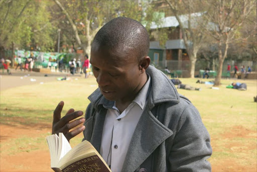 Philani Dladla is dubbed the Pavement Bookworm after seen reviewing books on Empire Road. Picture: Sowetan LIVE