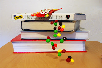 Photo: Requirement 4 (levitation): Skittles are tumbling off the stack of books, floating in mid-air! This levitation photo, created from a stack of 2 photographs and a ridiculous amount of Photoshop editing/manipulation, was a bit more difficult to create. I liked the concept a lot, but I forgot that I had to deal with the shadows created by the falling Skittles and perched Skittles bag. Fortunately, the set-up allowed me to see (and mostly replicate) the shadowed areas for a more realistic feel... Some of the clone/stamp tool could've been better used. I brightened the photo significantly but may have actually done too much.