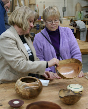 Photo: Lynda and Ingrid compare notes on Mark Verna's red oak natural-edge bowl with spalted sap wood.