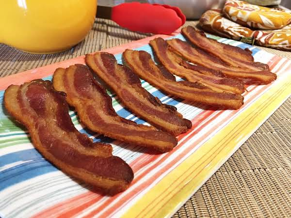 A Few Slices Of Cooked Bacon On A Serving Plate.