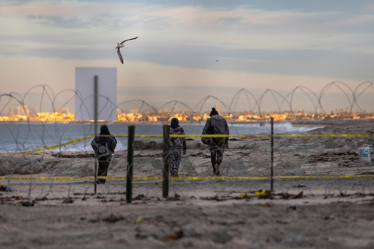 A migrant woman and two boys, part of a caravan of thousands from Central America trying to reach the United States, walk behind concertina wire on a beach in San Diego County after crossing illegally from Mexico to the U.S, photographed through a border wall from Tijuana, Mexico, December 4, 2018.