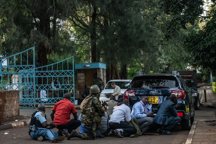 People take cover after hearing gunfire coming from the Dusit Hotel complex after being rescued on January 15, 2019 in Nairobi, Kenya. A current security operation is underway after terrorists attacked the hotel. Picture: GETTY IMAGES/ANDREW RENNEISEN