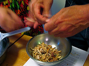 Photo: tearing toasted dried cuttlefish into small pieces
