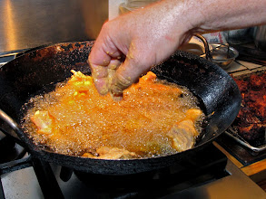 Photo: dropping the chicken into hot oil to fry