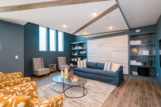 Clubhouse with wood-inspired flooring, blue walls, and seating
