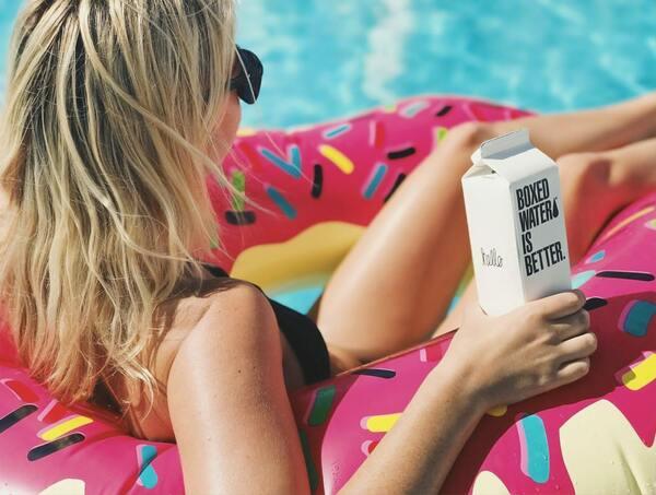 foto de uma mulher loira na piscina em cima de uma bóia segurando uma caixinha de água