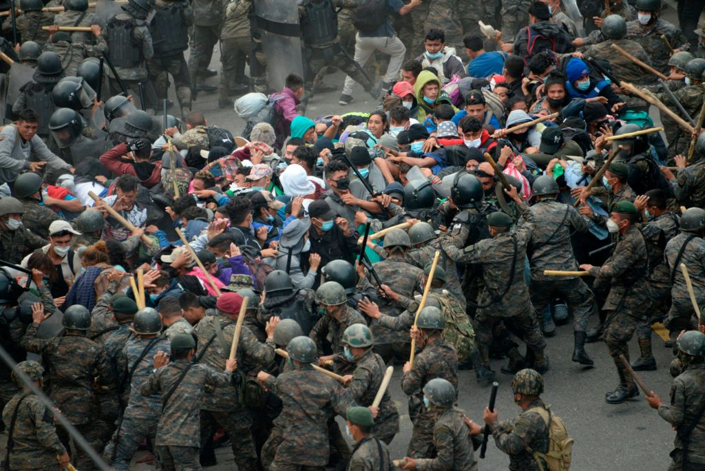 Honduran migrants, part of a caravan heading to the United States, clash with Guatemalan security forces in Vado Hondo, Guatemala on January 17, 2021. The reported $11 billion price tag to complete Trump's 567 mile southern border wall is dwarfed by the enormity of the more than $4 trillion in spending Joe Biden has earmarked in his first three months in office