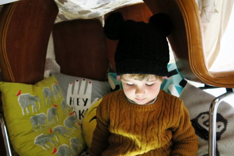 Little boy in pom pom hat