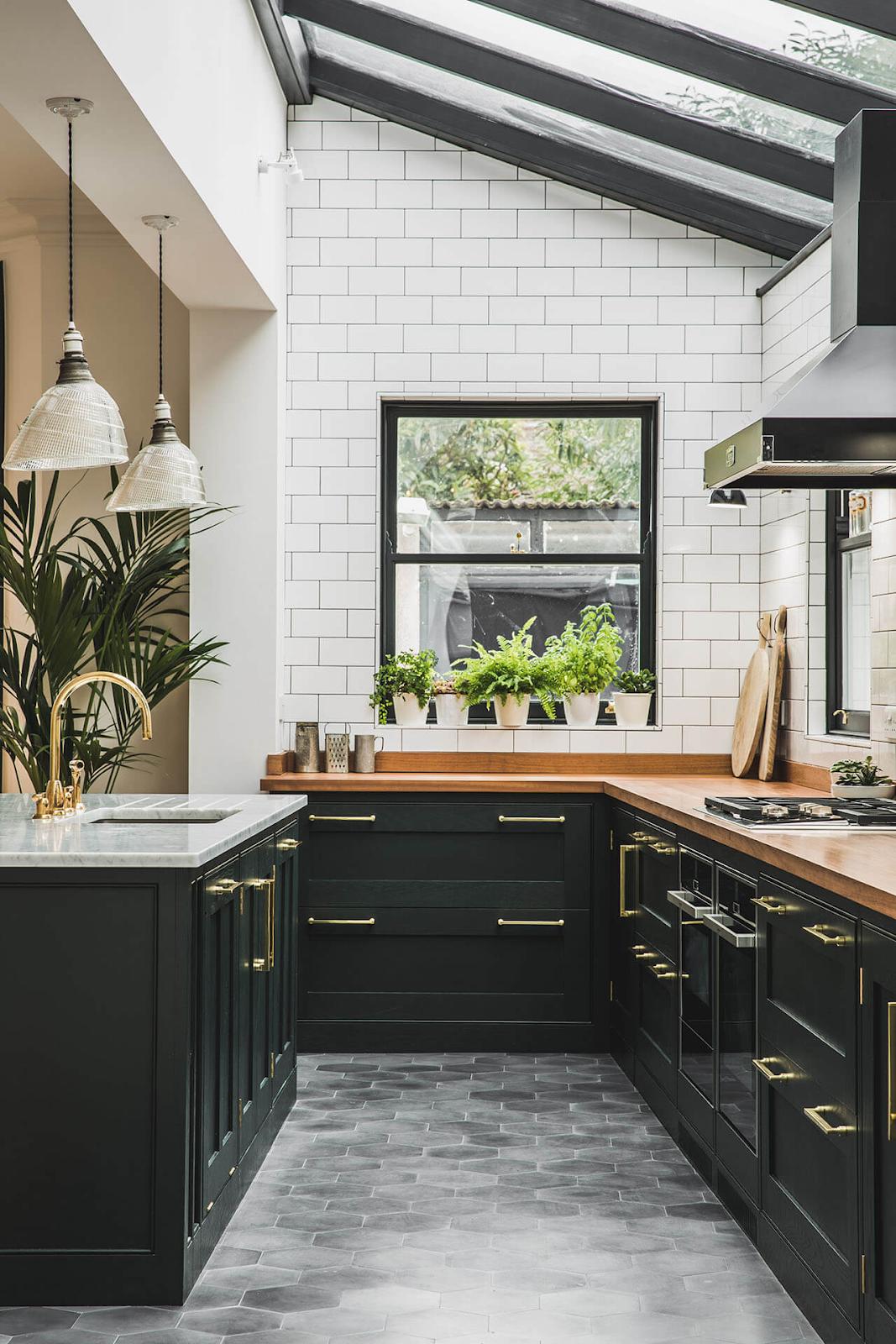 kitchen with skylits, plants, dark green shaker cabinets and white backsplash