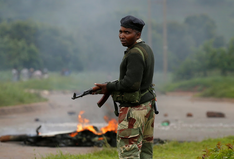 A soldier stands before a burning barricade during protests in Harare, Zimbabwe. SA is treating Emmerson Mnangagwa exactly as it used to treat Robert Mugabe: with sickening, immoral deference.