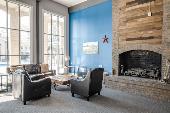 Community clubhouse seating area with large fireplace, plush seating, large windows, and a blue accent wall