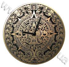 Photo: Часы на фоне календаря Майя. Пластик золотисто-черный, лазерная гравировка