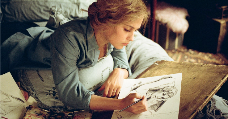 Alicia Vikander as Gerda Wegener in The Danish Girl. Gerda is lying on her front on a bed, holding a paintbrush. In front of her is a pencil sketch of Lili Elbe and a set of paints sitting on a wooden board.