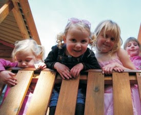 Toddlers leaning over railing and smiling for camera