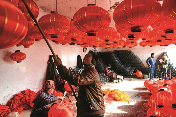 A worker hangs lanterns in a factory in Tuntou, southwest of Beijing, for Lunar New Year festivities planned for February 8. Known as the