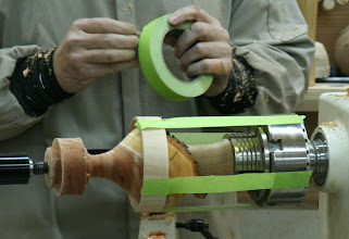 Photo: Taping a restraining ring to the chuck after reversing onto a jam chuck. This is not meant to handle any turning stresses -- just to keep the piece from flying off when separation is achieved -- beats a baseball glove.