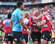 Malcolm Marx (R) of the Emirates Lions celebrates teammates after scoring a try during a Super Rugby semifinal match against the Waratahs at Ellis Park Stadium, Johannesburg on July 28 2018.