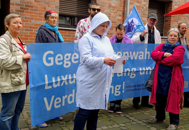 Demonstrierende in Bademänteln mit Trasparent: «Gegen Mietenwahnsinn, Luxussanierung und Verdrängung! Initiative Recht auf Stadt Köln».