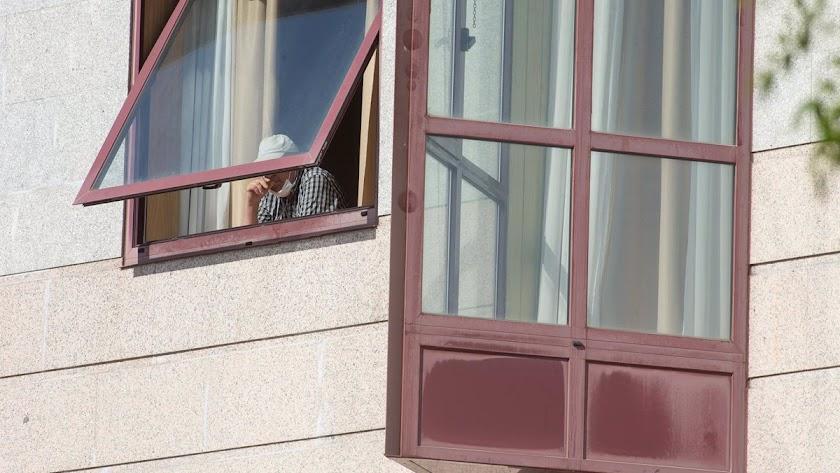 Un anciano de una residencia se asoma a través de la ventana.