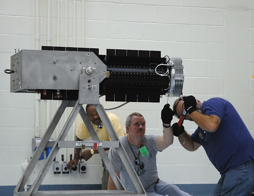 Mervin Smith watches as technicians install a flight adapter on the radioisotope thermoelectric generator RTG.