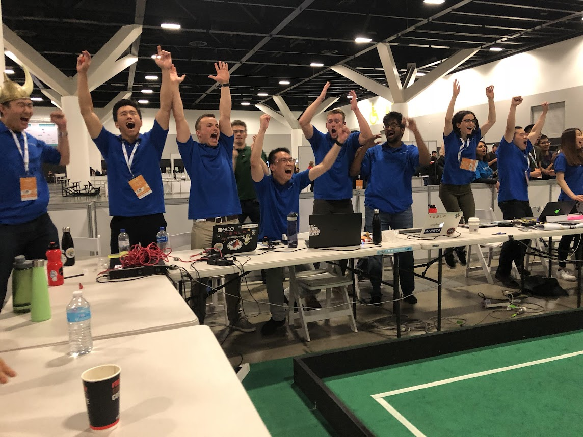 Group of students wearing blue shirts and cheering in a robotics competition