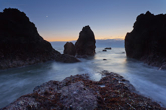 Photo: A small crescent moon sets over the rocks in Rodeo Cove.