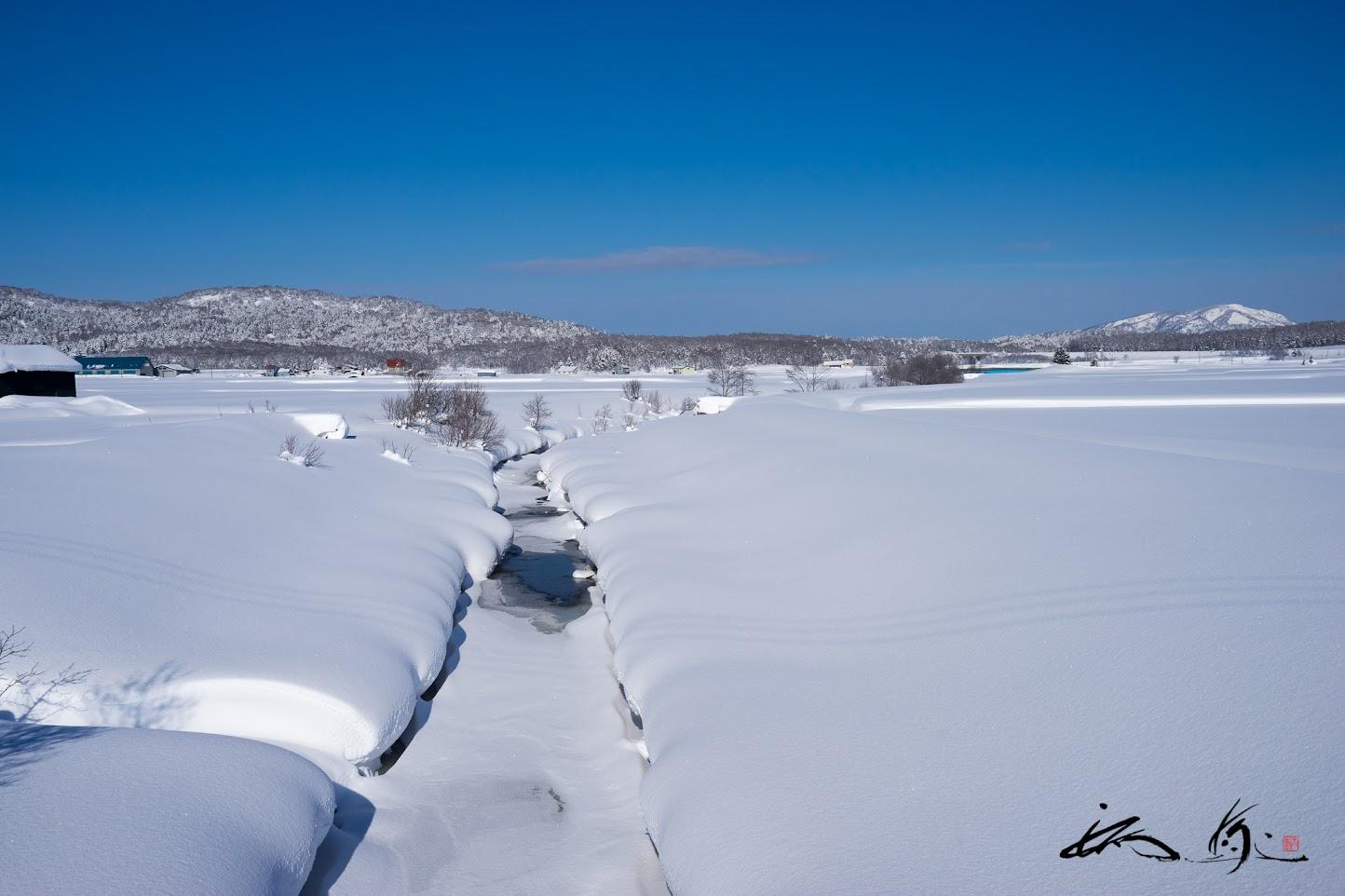 雪に埋もれる川面