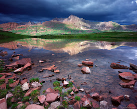 Photo: Afternoon sunlight beams on the Maroon Bells fourteeners, as seen from high in Fravert Basin - July.<br><br>The dark storm clouds were starting to rumble, so immediately after taking this picture, I packed up my gear as quickly as possible and ran a half mile to the shelter of the nearest trees.  The next three or four hours were spent inside the tent listening (and feeling) the cracking booms of lightning and thunder.