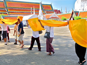 Photo: worshippers carrying the long length of holy cloth follow