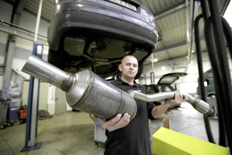 A worker at Twintec, in Königswinter, Germany, with a soot filter catalyst. Catalytic converters for cars use platinum, palladium and rhodium. Picture: GETTY IMAGES