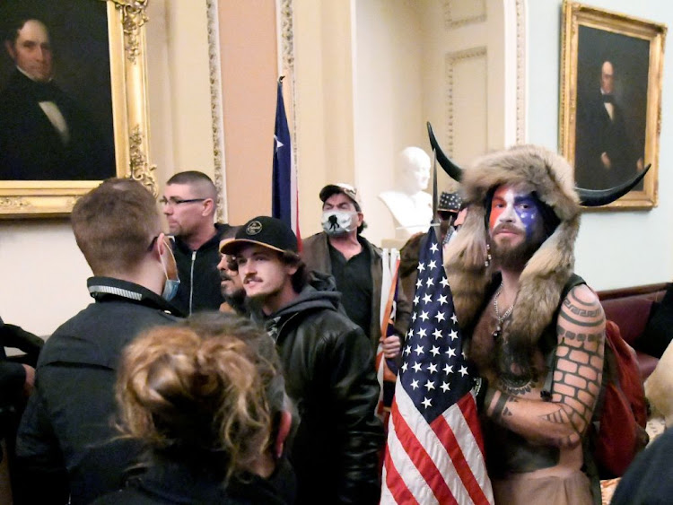 Jacob Anthony Chansley, also known as Jake Angeli, of Arizona, stands with other supporters of US President Donald Trump as they demonstrate on the second floor of the US Capitol building after breaching security defences, in Washington, US, on January 6 2021.