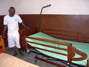 Photo: le Docteur Firmin Gbessinon est fier devant le lit électrique provenant de Grandcamp