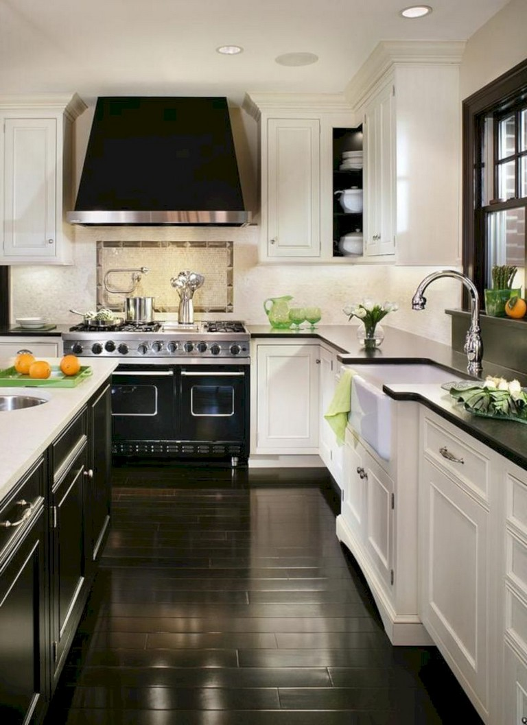glamorous contemporary kitchen with white cabinets and black countertops. a dark wood floor accentuates the drama of the space in addition to black appliances and a black range hood