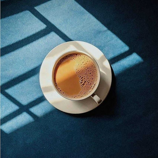 An overhead view of a cup of coffee set on a blue table cast in window light.