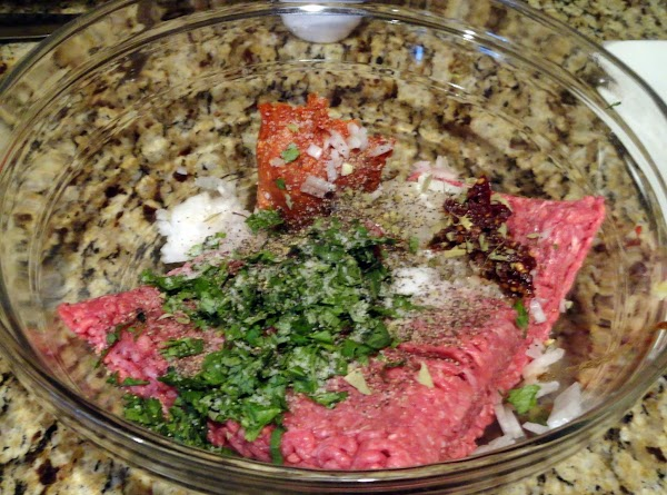 In a large bowl, combine ground beef, sundried tomatoes (reserve oil for brushing on...