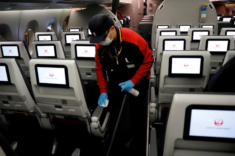 A staff member of Japan Airlines wearing a protective face mask and gloves cleans the cabin of a plane after a domestic flight in Tokyo, Japan, in this May 26 2020 file photo. Picture: REUTERS/Kim Kyung-Hoon