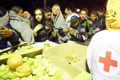 Crunch for refugees: Hungarian Red Cross provide food to migrants walking towards the Austrianborder at Hegyeshalom, Hungary, yesterday. Tens of thousands of migrants, most of them fleeing warand hardship in Syria, are trying to reach Western Europe.
