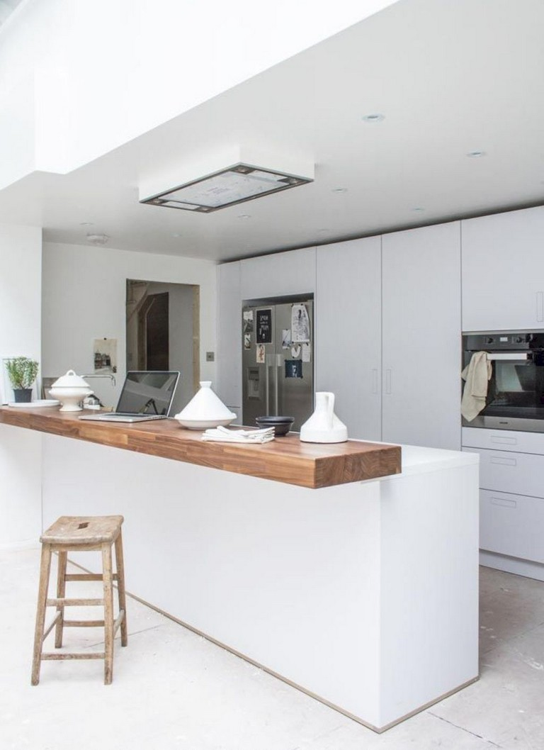 A square barstool matches the visual tone of this sleek modern white kitchen