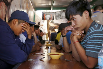 Photo: Men pray before eating dinner at the Aid Center for Deported Migrants in Nogales, Sonora, Mexico, March 31. Dinner that evening was served by visiting U.S. bishops', including Auxiliary Bishop Luis Zarama of Atlanta, pictured at far left. The center, run by the Kino Border Initiative, was one stop the bishops made during their tour of the border area near Nogales. (CNS photo/Nancy Wiechec) (April 1, 2014)