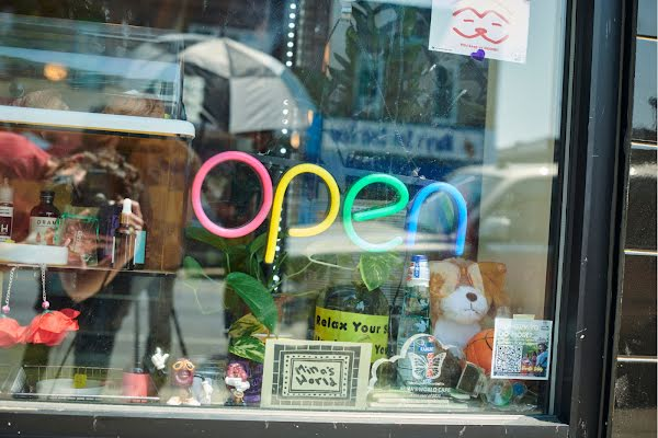 """A rainbow neon sign reads """"Open"""" in the window of a whimsical cafe"""