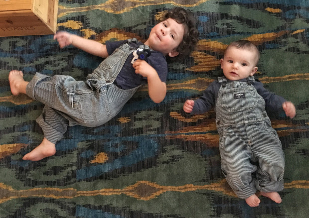 Toddler and baby boys laying on floor