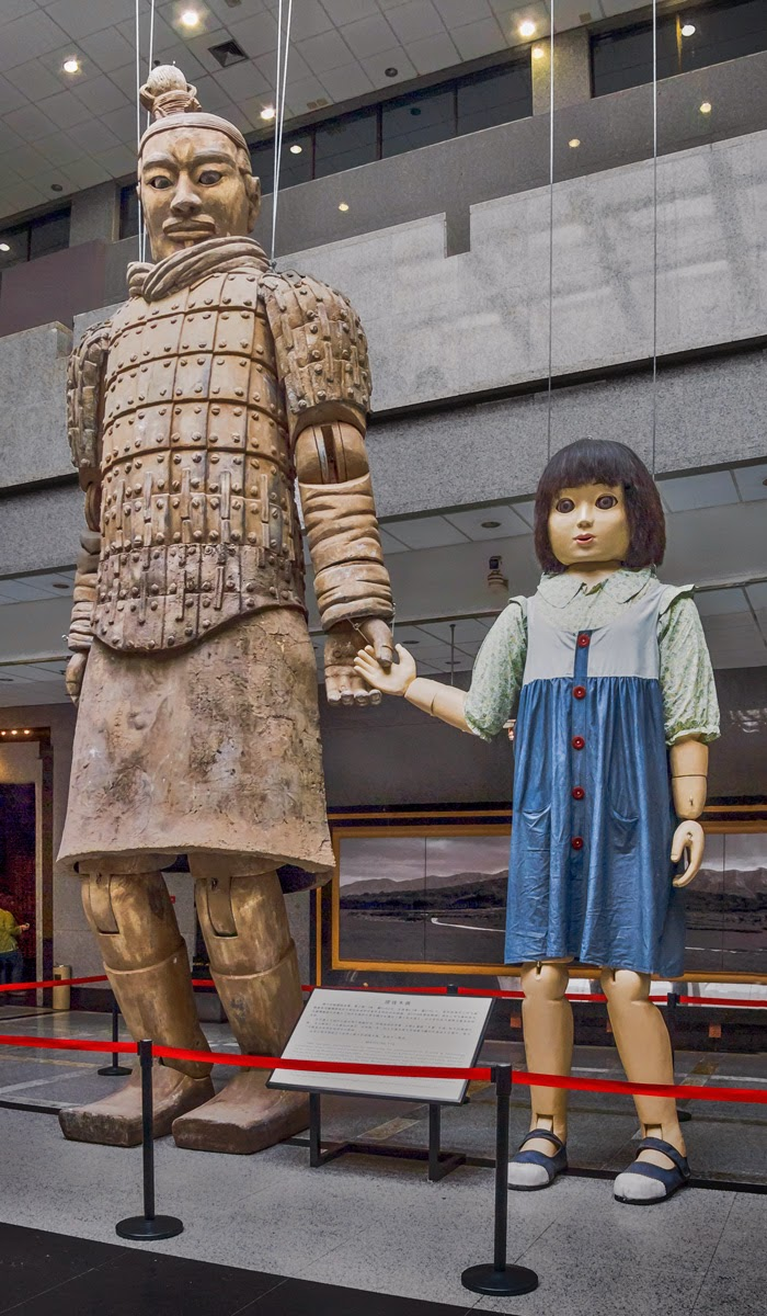 """Photo: Giants Among Us But it seems someone else is pulling the strings.  That big terracotta guy staring down at you is a tad unnerving, but he'd have to break his strings to chase anyone down. He seems, perhaps, kindhearted, seeing as he's looking after the """"little"""" one.  Apparently these giant marionettes were used in the opening ceremonies of the 2008 Beijing Olympics, but now they are on display at the Terracotta Warrior excavation site museum, Lintong District, Xian, ShiaanxiProvince, China. Keeping in mind that the perimeter stanchions are typically 37 to 40 inches tall, you get some idea of their size.  #Travel  #China  #Xian  #TerracottaWarriors"""