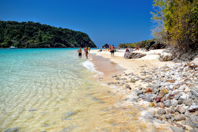 Walk on the white sand beach of Laem Thong with its unique round stones