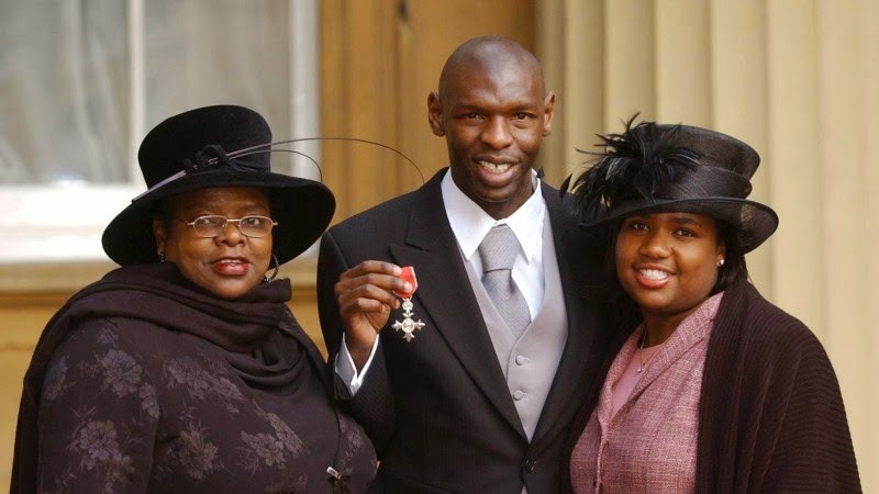 Photo: Footballer Shaun Goater holds the MBE he received at Buckingham Palace, London, with his mother Lynette and wife Anita.