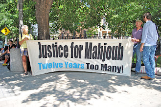Photo: Supporters hold up a banner in front of the court house.
