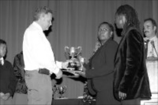 EMOTIONAL TRIBUTES: Maduo Mafubedu's mother, Masodi, and brother, Thato, receive awards from school principal Andre Nel on her behalf, Maduo, a pupil at Randeir High School in Winchester Hills south of Johannesburg, was raped and killed by thugs. Pic. Elvis Ntombela. 24/04/2007. © Sunday World.