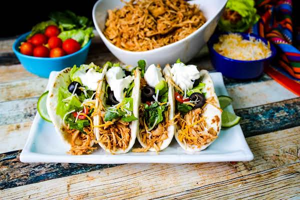Slow Cooker Shredded Taco Chicken Made Into Tortillas.