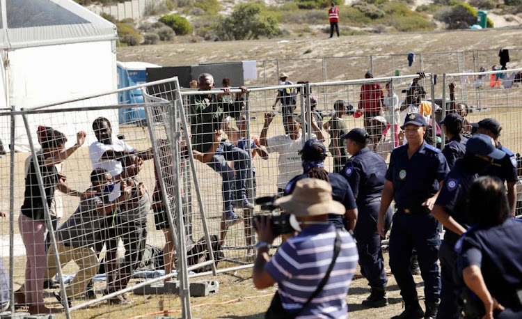 City of Cape Town officials try to maintain order as homeless people break down a barricade during a media tour of the controversial Strandfontein facility which houses the homeless during the Covid-19 lockdown.