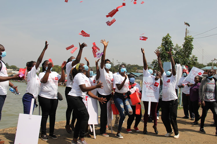 People at Aids Healthcare Foundation toss packets of condoms as they celebrate International Condom Day in Homa Bay on February 12.