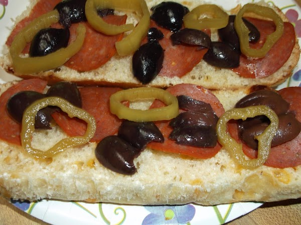 On split side of roll; arrange/layer the pepperoni, pepperoncini, and olives.